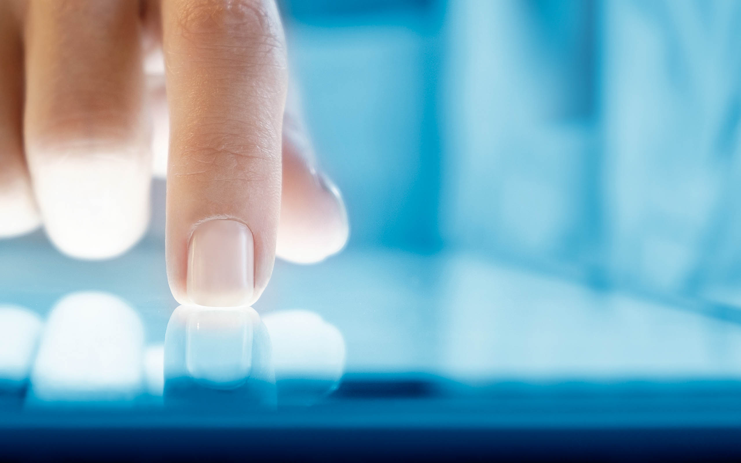 Finger on touch-screen blue tablet.
