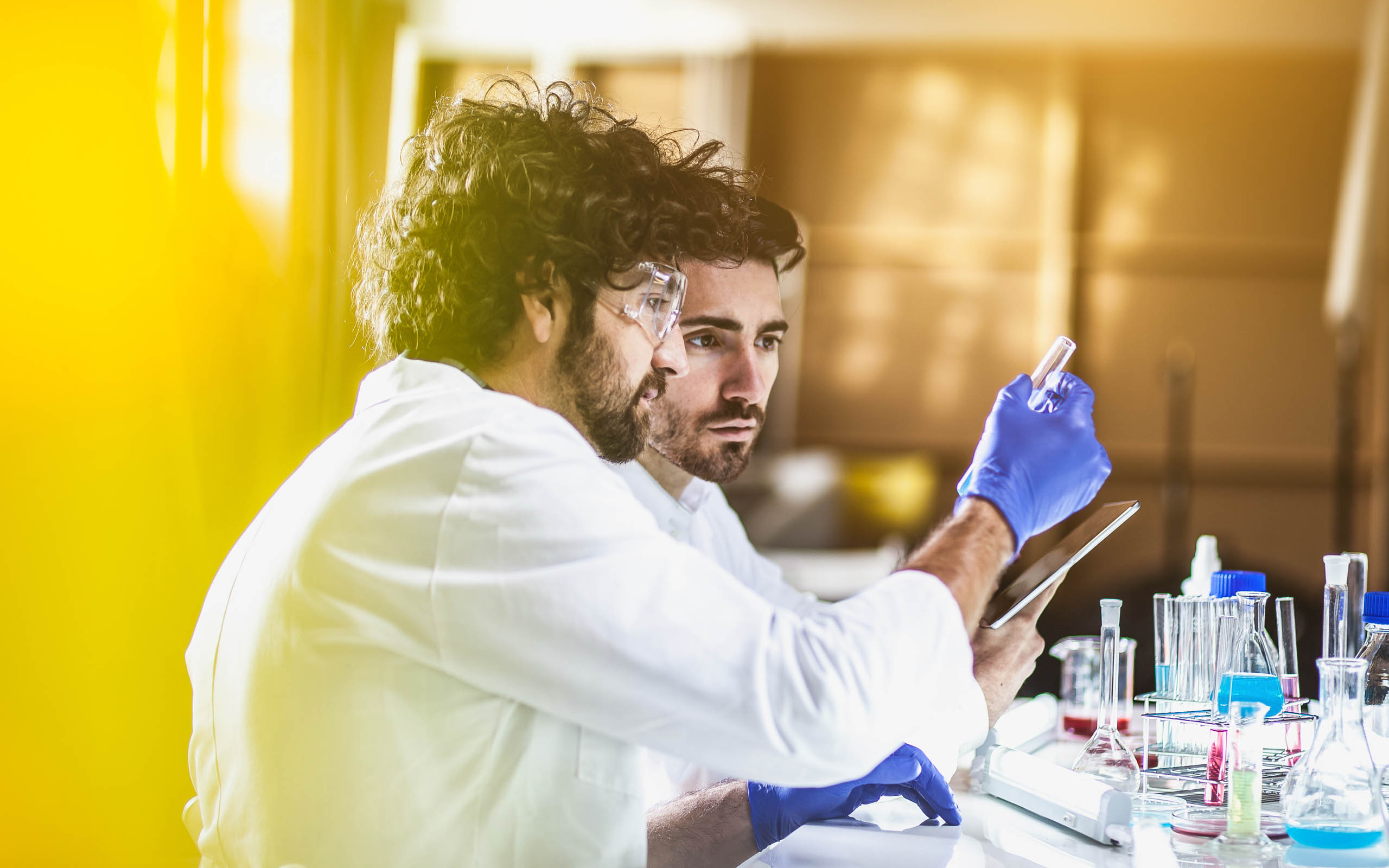 Two male scientists using cell therapy software on a tablet to record testing data.